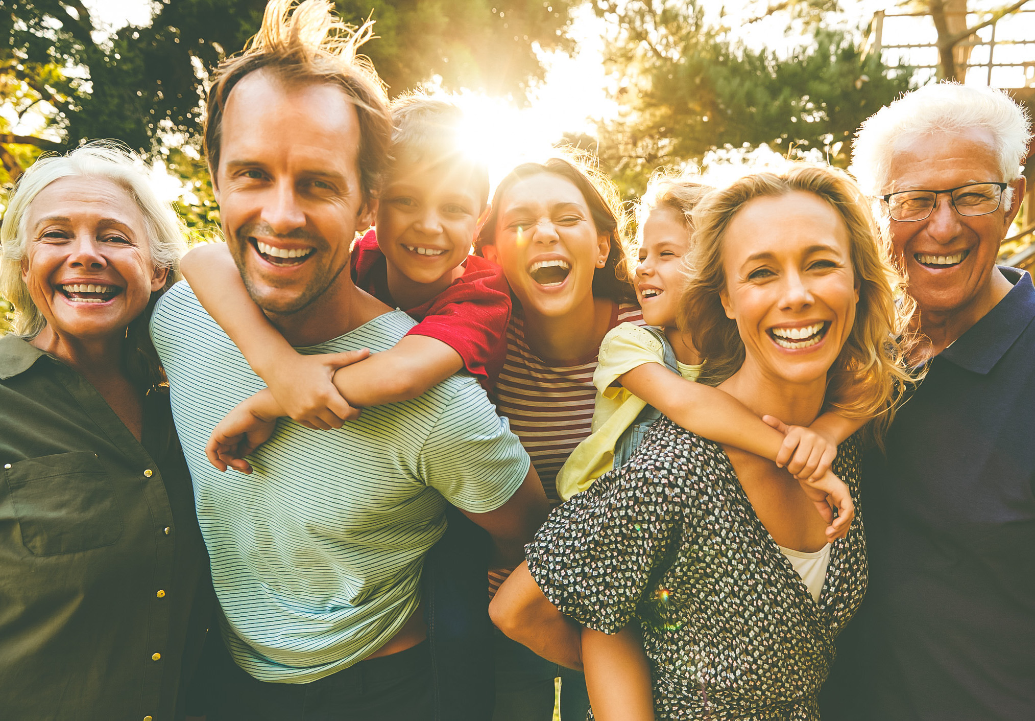 Outdoor Portrait Of Multi-Generation Family Walking In Countryside Against Flaring Sun